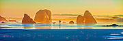 Photographic panorama of a man walking his dog amid monolithic rocks at dawn on Bandon Beach, Oregon