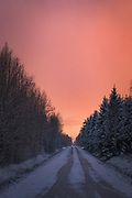 Snow and ice covered gravel road going through young forest stands with colorful sunset sky and snowfall overhead, Nīcgale, Latvia Ⓒ Davis Ulands | davisulands.com