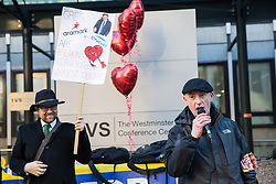 London, UK. 14th February, 2019. Chip Hamer, also known as Grim Chip, of Poetry on the Picket Line performs for outsourced support staff from the Public & Commercial Services (PCS) union on a Valentine's Day-themed picket line outside the Department of Business, Energy and Industrial Strategy (BEIS) during strike action to demand the London Living Wage and an end to outsourcing.