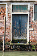 A weathered blue door is stained green by Venice Lagoon tides. Venice (Venezia), founded in the 400s AD, is capital of Italy's Veneto region, named for the ancient Veneti people from the 900s BC. The romantic City of Canals stretches across 100+ small islands in the marshy Venetian Lagoon along the Adriatic Sea, between the mouths of the Po and Piave Rivers. The Republic of Venice was a major maritime power during the Middle Ages and Renaissance, a staging area for the Crusades, and a major center of art and commerce (silk, grain and spice trade) from the 1200s to 1600s. The wealthy legacy of Venice stands today in a rich architecture combining Gothic, Byzantine, and Arab styles. Venice and the Venetian Lagoon are honored on UNESCO's World Heritage List.