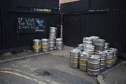 Empty beer kegs outside a bar in Hoxton, London, UK. This scene also contains some of the local ironic street art graffiti. Reading: If love were the drug, I want to OD.