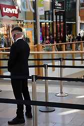 Security guard wearing a mask outside the Apple shop in Chapelfield shopping centre, Norwich UK, during Coronavirus pandemic. Shoppers have their temperature taken before they are allowed to enter the shop. Sep 2020