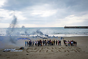 Local residents and members of an Kent's Anti-Racism Network peacefully stand behind 'Refugees Welcome' written in the sand on Sunny Sands Beach, Folkestone, Kent, UK.  This demonstrations was organised in response to reports that members of the far-right group, Britain First, have started patrolling beaches around Dover and Folkestone to try to catch migrants crossing the channel in small boats.  (photo by Andrew Aitchison / In Pictures via Getty Images)