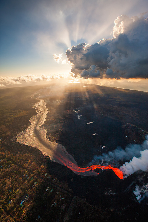 Kilauea's east rift zone: Spectacular crepuscular rays illuminate the early morning sky over Leilani Estates and fissure 8. Photo charter service provided by Paradise Helicopters.