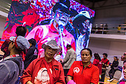"23 FEBRUARY 2014 - NAKHON RATCHASIMA (KORAT), NAKHON RATCHASIMA, THAILAND: People gather around a large closed circuit TV at the Red Shirt meeting in Korat. The United front of Democracy against Dictator (UDD or Red Shirts), which supports the elected government of Yingluck Shinawatra, staged the ""UDD's Sounding of the Battle Drums"" rally in Nakhon Ratchasima (Korat) to counter the anti-government protests that have gripped Bangkok since November. Around 4,000 of UDD's regional and provincial coordinators along with the organization's core members met at Liptapunlop Hall inside His Majesty the King's 80th Birthday Anniversary Sports Complex in Korat to discuss the organization's objectives and tactics against anti-government protestors, which the UDD says ""seek to destroy the country's democracy."" The UDD leadersa announced that they will march to Bangkok and demonstrate against anti-government protests led by Suthep Thaugsuban.   PHOTO BY JACK KURTZ"