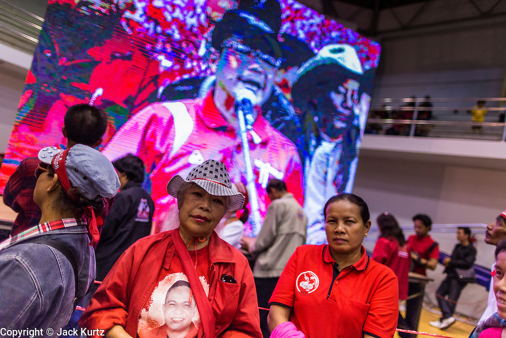 """23 FEBRUARY 2014 - NAKHON RATCHASIMA (KORAT), NAKHON RATCHASIMA, THAILAND: People gather around a large closed circuit TV at the Red Shirt meeting in Korat. The United front of Democracy against Dictator (UDD or Red Shirts), which supports the elected government of Yingluck Shinawatra, staged the """"UDD's Sounding of the Battle Drums"""" rally in Nakhon Ratchasima (Korat) to counter the anti-government protests that have gripped Bangkok since November. Around 4,000 of UDD's regional and provincial coordinators along with the organization's core members met at Liptapunlop Hall inside His Majesty the King's 80th Birthday Anniversary Sports Complex in Korat to discuss the organization's objectives and tactics against anti-government protestors, which the UDD says """"seek to destroy the country's democracy."""" The UDD leadersa announced that they will march to Bangkok and demonstrate against anti-government protests led by Suthep Thaugsuban.   PHOTO BY JACK KURTZ"""