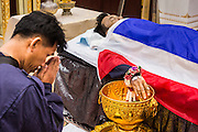 19 FEBRUARY 2014 - BANGKOK, THAILAND: Police officers pay respects at the bathing rites for Police Senior Sgt-Major Phianchai Pharawat, 45. Bathing rites are the first step in Buddhist funeral ritual. Phianchai was killed by anti-government protestors Tuesday during an altercation between protestors and police. Four people were killed and more than 60 hospitalized as a result of the fighting. Anti-government protestors aligned with Suthep Thaugsuban and the People's Democratic Reform Committee (PRDC) attacked police officers who tried to clear protestors out of sites they've occupied since January.    PHOTO BY JACK KURTZ