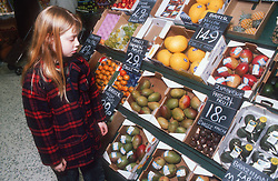 Young girl looking at fruit in supermarket,