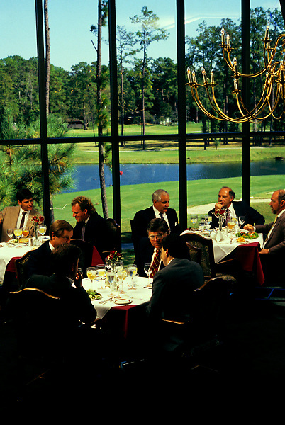 Stock photo of nicely dressed men eating lunch at a restaurant on a golf course