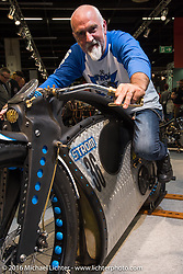 Noel Connolly on his hard tail frame 2015 Strom Zero-Emission electric motorcycle from Flame-Art Designs in County Galway, Ireland on display in the AMD World Championship of Custom Bike Building in the custom themed Hall 10 AMD World Championship of Custom Bike Building show in the custom dedicated Hall 10 at the Intermot Motorcycle Trade Fair. Cologne, Germany. Saturday October 8, 2016. Photography ©2016 Michael Lichter.
