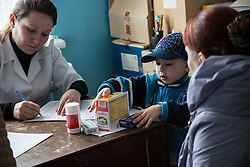 Maxim, 5, and his mother collect medicines after a consultation at the MSF mobile clinic in the town of Sukodolsk near to Lugansk.