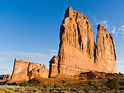 The orange sandstone Courthouse Towers resist erosion in Arches National Park, Utah, USA. These rock monuments are beautiful both at sunrise (seen here) and sunset. The Courthouse Towers are comprised of the Slick Rock member of Entrada Sandstone above the red-brown. or chocolate-brown marker beds of the Dewey .Bridge member.