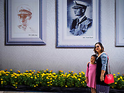 18 FEBRUARY 2017 - BANGKOK, THAILAND: A woman and child in front of  portraits of Bhumibol Adulyadej, the Late King of Thailand, hanging in front of Paragon shopping mall in Bangkok. The revered monarch died on Oct. 13, 2016 and will be cremated on Oct 25, 2017. Thailand's mourning period ends on October 29, 2017.     PHOTO BY JACK KURTZ