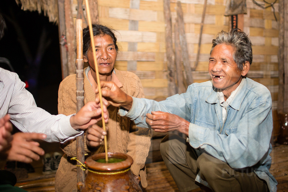 Portrait of a happy man sharing rice wine with friends, Loc Bac, Vietnam, Southeast Asia