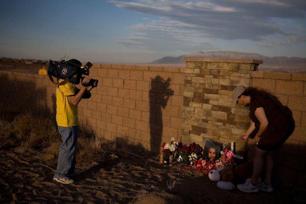 Photo by Steven St. John..A neighbor leaves a stuffed animal at the memorials honor Gina Michelle Valdez and Victoria Chavez as a television camera person films. Investigators search for additional human remains on Monday, March 2, 2009 on the southwestern outskirts of Albuquerque, N.M. at the site of a planned residential subdivision. Investigators and forensics experts are searching the crime scene where the remains of at least 13 bodies have been uncovered. The discovery has opened up cases involving missing prostitutes, some of whom vanished as much as 20 years ago.