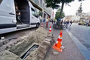 Nederland, Nijmegen, 20-8-2019 Glasvezelnetwerk. Winkels en woningen worden aangesloten op het glasvezelnet. Op de foto is een installatiemonteur in een busje bezig de kabels te verbinden, lassen, met de hoofdkabel die naar de centrale loopt. Modern supersnel netwerk waarop aanbieders van internet, digitale tv en telefonie hun diensten kwijt kunnen. Foto: Flip Franssen