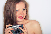 Portrait of a young woman taken in an apartment in South Bristol. She is holding a camera and smiling at the camera. Image was taken by versatile portrait photographer Jonathan Bowcott who is based in Bristol UK