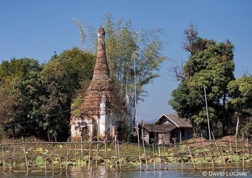 """View on an old stupa near the shore of Inle Lake. According to """"Wikipedia"""" - The stupa is the latest Buddhist religious monument and was originally only a simple mound of mud or clay to cover supposed relics of the Buddha (cetiya). After the parinirvana of the Buddha, his remains were cremated and the ashes divided and buried under eight stupas with two further stupas encasing the urn and the embers. Little is known about these early stupas, particularly since it has not been possible to identify the original ten monuments. However, some later stupas, such as at Sarnath and Sanchi, seem to be embellishments of earlier mounds."""