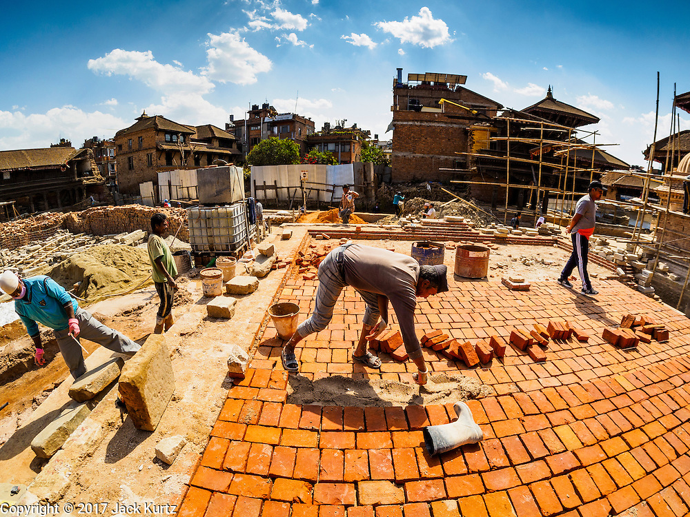03 MARCH 2017 - BHAKTAPUR, NEPAL: Workers rebuilding one of the Hindu temples in Bhaktapur's Durbur Square. Bhaktapur, a popular tourist destination and one of the most historic cities in Nepal was one of the hardest hit cities in the earthquake. Recovery seems to have barely begun nearly two years after the earthquake of 25 April 2015 that devastated Nepal. In some villages in the Kathmandu valley workers are working by hand to remove ruble and dig out destroyed buildings. About 9,000 people were killed and another 22,000 injured by the earthquake. The epicenter of the earthquake was east of the Gorka district.      PHOTO BY JACK KURTZ