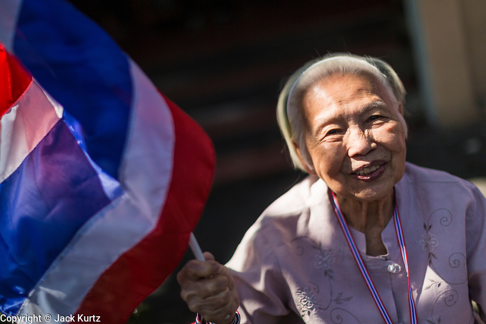 """15 JANUARY 2014 - BANGKOK, THAILAND: An elderly woman waits for anti-government protest leader Suthep Thaugsuban in Bangkok. Tens of thousands of Thai anti-government protestors continued to block the streets of Bangkok Wednesday to shut down the Thai capitol. The protest, """"Shutdown Bangkok,"""" is expected to last at least a week. Shutdown Bangkok is organized by People's Democratic Reform Committee (PRDC). It's a continuation of protests that started in early November. There have been shootings almost every night at different protests sites around Bangkok. The malls in Bangkok are still open but many other businesses are closed and mass transit is swamped with both protestors and people who had to use mass transit because the roads were blocked.    PHOTO BY JACK KURTZ"""