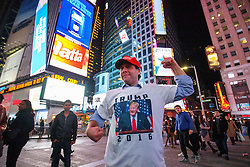 © Licensed to London News Pictures. 09/11/2016. New York CIty, USA. A man wearing a pro-Trump t-shirt reacts to news that Donald Trump is elected as the next president of the United States, while gathering in Times Square, New York City, on Wednesday, 9 November. Photo credit: Tolga Akmen/LNP