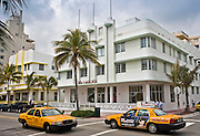 Yellow taxi cabs by The Carlyle condo on Ocean Drive, South Beach, Miami, Florida, USA