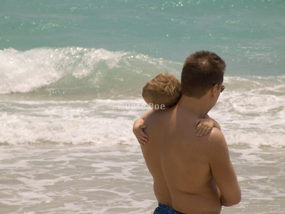 Father holding his sleeping son in the arms while at the beach Miami USA