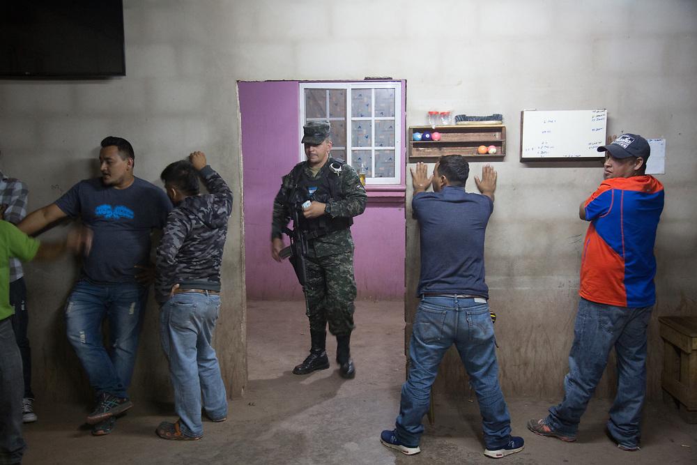 Military Police search a billiards hall in La Era neighbourhood of Tegucigalpa
