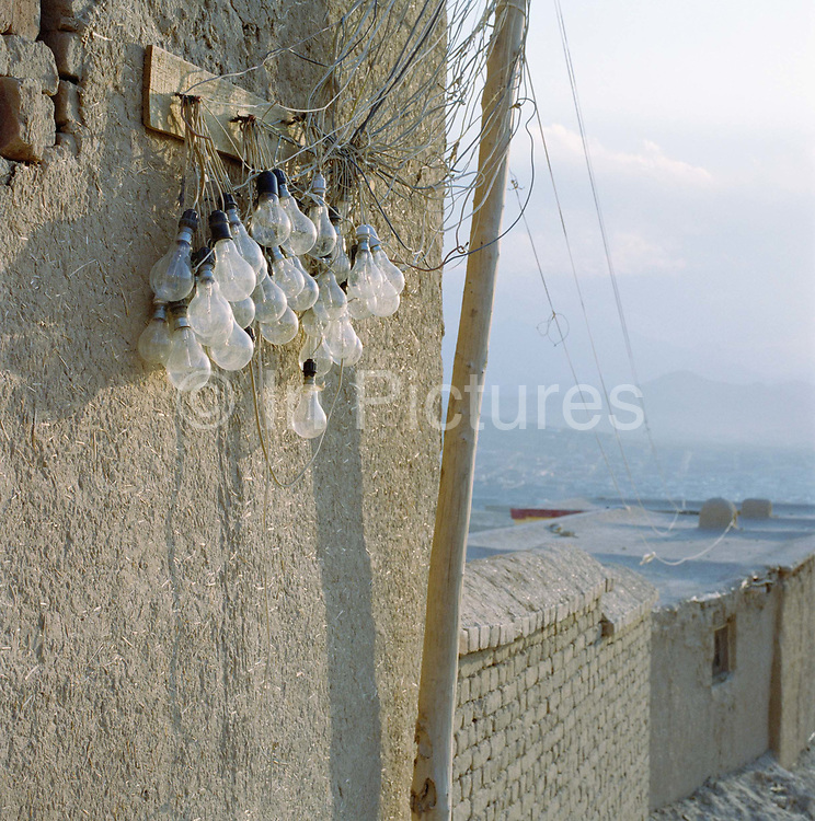 Bulbs wired to a generator indicate power to individual homes on this rudimentary housing estate on a mountain in north Kabul.