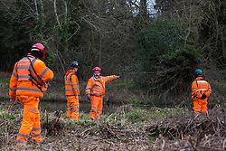 Denham, UK. 4 February, 2020. Engineers and security guards walk across land cleared for works for the HS2 high-speed rail link project in front of the river Colne. Planned works in the immediate vicinity are believed to include the felling of 200 trees and the construction of a roadway, Bailey bridge, compounds, fencing and a parking area. The other side of the river lies within a wetland nature reserve adjacent to a Site of Metropolitan Importance for Nature Conservation (SMI).