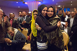 © Licensed to London News Pictures. 01/05/2015. London, UK. Councillor, Rabina Khan reacts as she hears ex Mayor of Tower Hamlets, Lutfur Rahman endorce her as his proposed candidate at a public meeting held at the Waterlily in Stepney, east London on 30th April 2015. The meeting was ex Mayor of Tower Hamlets, Lutfur Rahman's first public appearance after being found guilty of electoral fraud last week and called for attendees to donate money to a legal fund to facilitate an appeal against the High Court ruling. Photo credit : Vickie Flores/LNP