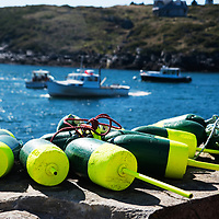 Close up view of lobster trap buoys on the dock at Monhegan Island. Manana Island in the background, behind the lobster boats.