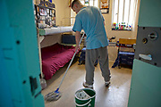 An 'enhanced' prisoner mopping his cell on H wing at the Young Offenders Institution in Aylesbury, United Kingdom. Under the Incentives and Earned Privilege Scheme, prisoners in the UK can earn extra privileges for good behaviour such as wearing their own clothes, having televisions in their cells, and having more free time to socialise. They are often housed together in their own wing. There are three levels of earned privileges - Basic, Standard and Enhanced. HMYOI / HM Prison Aylesbury (Her Majesty's Young Offender Institution Aylesbury) is a prison is operated by Her Majesty's Prison Service.