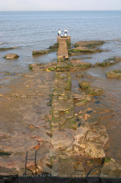 Two men sitting on a pier jetty towards the horizon fishing and looking at the sea. Broken stone path leading out in the water., on the riverside seaside walk along the river Rio de la Plata Ramblas Sur, Gran Bretagna and Republica Argentina Montevideo, Uruguay, South America