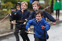 © Licensed to London News Pictures. 09/02/2016. Ilkley, UK. Competitors in this year's pancake race in Ilkley, West Yorkshire, dash towards the finish line, flipping their pancakes as they go. The race is held annually in the Yorkshire town of Ilkley on Shrove Tuesday. Photo credit : Ian Hinchliffe/LNP
