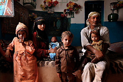"""Fatima sits with her husband and four children in Hajjah, Yemen, July 28, 2010. It is unclear what age she is now, but Fatima says she was married around the age of 8 and started having children right after her menstruation. She has had two children die during pregnancy and guesses she is now about 22 years old. """"What has happened to me is horrible. People should at least let young girls wait until their first period,"""" she said."""