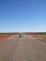 The Royal Flying Doctor Service emergeny airstrip is a part of the highway in parts of Western Australia. A bicycle rider is on the airstrip