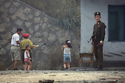 A soldier wearing two gold wrist watches stands guard as a family passes in the town of Sunuiju October 10, 2006.  DPRK, north korea, china, dandong, border, liaoning, democratic, people's, rebiblic, of, korea, nuclear, test, rice, japan, arms, race, weapons, stalinist, communist, kin jong il