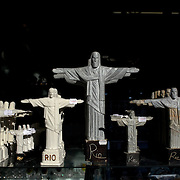Statues of Christ the Redeemer on sale in the souvenir shop on site. The iconic Cristo Redentor, Christ the Redeemer statue sits atop the mountain Corcovado. The Christ statue was voted one of the seven wonders of the modern world in 2007. It was designed by Brazilian Heitor de Silva Costa and was inaugurated in 1931 having taken years to assemble. Rio de Janeiro, Brazil. 21st July 2010. Photo Tim Clayton..