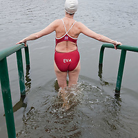 LONDON, ENGLAND - DECEMBER 25: A member of the Serpentine Swimming Club enters the icy Serpentine waters during the annual Christmas Day Peter Pan Cup on December 25, 2009 in London, England.  The traditional 100 yards Christmas race got its name in 1904 after Sir James Barrie presented the first Peter Pan Cup and is only open to club members who have competed in at least three of the winter series races.   (Photo by Marco Secchi/Getty Images)