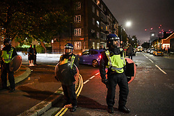 © Licensed to London News Pictures. 03/07/2020. London, UK. Riot police react to a block party that moved through boroughs in west London ending in White City estate in the early hours of July 4th. A date that coincides with relaxing of rules, dubbed 'Super Saturday', permitting pubs and restaurants to serve alcohol for first time since restrictions were imposed earlier in the year in response to the coronavirus pandemic. Photo credit: Guilhem Baker/LNP