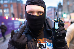 """© Licensed to London News Pictures. 20/03/2021. Manchester, UK. A man with a police radio that was pulled from a police officer's uniform . A """" Kill the Bill """" and Reclaim the Streets protest demonstration is held in St Peter's Square in Manchester City Centre in opposition to the Police, Crime, Sentencing and Courts Bill 2021 that is currently before Parliament and after the death of Sarah Everard in London . Photo credit: Joel Goodman/LNP"""