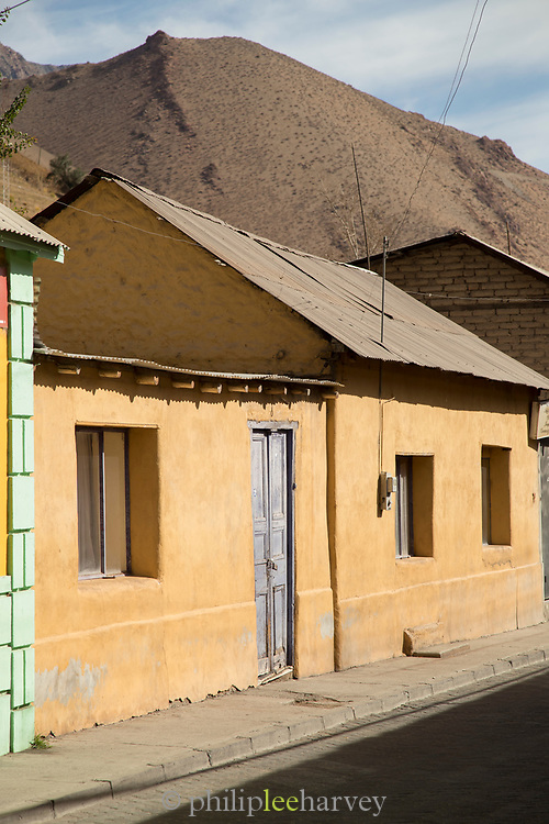 House on town street and mountains on background, Pisco Elqui, Chile