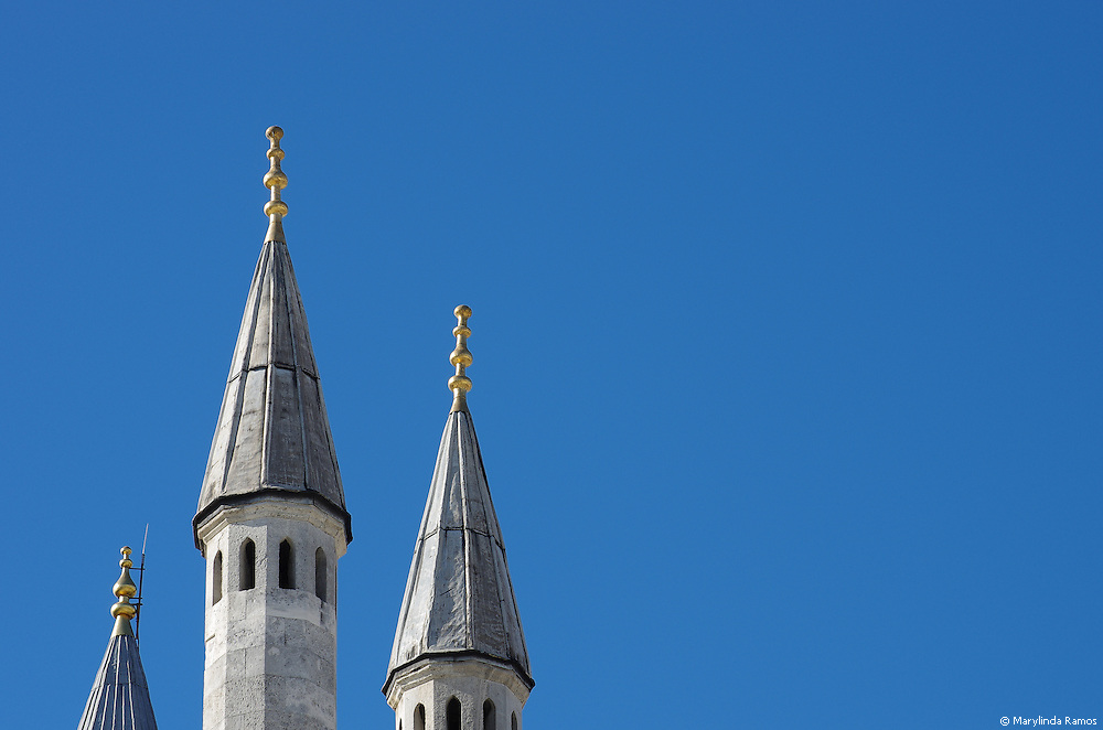 Three spires set against a clear blue sky as seen from the Harem courtyard at Topkapi palace in Istanbul, Turkey.