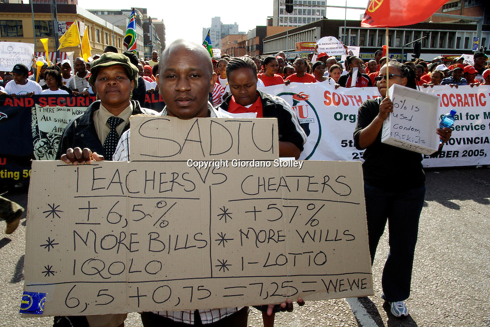 DURBAN - 13 June 2007 - Striking government workers march through central Durban, including this one whose placard makes the comparison between teachers and and cabinet ministers..Striking government workers, including nurses are demanding 12 percent but so far the government has only offered 7.25 percent..Picture: Giordano Stolley/Allied Picture Press