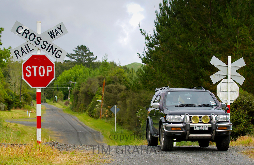 4-wheel drive off road vehicle at railway crossing with traffic signs, North Island, New Zealand
