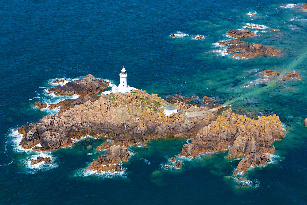 Aerial view of Corbiere lighthouse and the rocks surrounding it at high tide on a sunny day in Jersey, Channel Islands