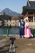 A young Korean couple in Hanboks, traditional Korean dress, pose for a photo at the Gyeongbokgung Palace on 26th February 2018 in Seoul, South Korea. Gyeongbokgung, also known as Gyeongbokgung Palace or Gyeongbok Palace, was the main royal palace of the Joseon dynasty. Built in 1395, it is located in northern Seoul.