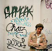 Greek-born writer of foward-fiction, Panos Karnezis in London where he lives and writes stands by a wall covered in urban graffiti with arms folded and a slightly mischevious look i his dark eyes. Author of Little Infamies (2002), The Maze (2004) and the Convent (2010) he is a developing writer of prize-winning fiction, shortlisted for the Whitbread First Novel for the acclaimed Little Infamies. Panos Karnezis was born in Greece in 1967 and came to England in 1992. He studied engineering and worked in industry, then studied for an MA in Creative Writing at the University of East Anglia.