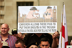 © Licensed to London News Pictures.  20/09/2014. LONDON, UK. A  member of the English Defence League (EDL) holds a placard during a rally opposite Downing Street. The group is attempting to highlight it belief that  Muslim sexual grooming gangs are abusing English girls. Earlier this week a home office official warned of the rise of the far right. Photo credit: Cliff Hide/LNP